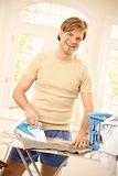 Laughing guy at ironing stand. Stock Photography