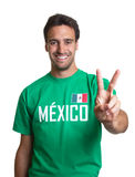 Laughing guy in a mexican jersey showing victory sign. Laughing guy in a mexican soccer jersey showing victory on an isolated white background Stock Photos