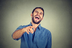 Laughing guy pointing with finger at camera Stock Image