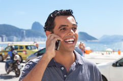 Laughing guy at Rio de Janeiro at phone. Laughing guy at Rio de Janeiro speaking at phone with Sugarloaf Mountain and ocean in the background Royalty Free Stock Photography