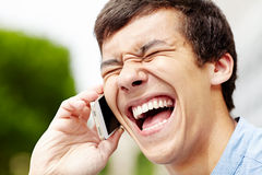 Laughing guy with smartphone closeup Stock Image