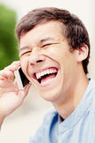 Laughing guy with smartphone headshot Royalty Free Stock Images