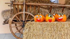 Laughing Halloween Pumpkins. Painted Halloween Pumpkins arranged on a hay bale in front of a wooden carriage Stock Image