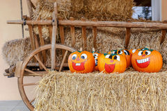 Laughing Halloween Pumpkins. Painted pumpkins arranged on a hay bale with wooden carriage Stock Photo
