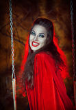 Laughing halloween woman in red cloak on the swing Stock Photos
