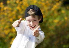 Laughing handsome boy posing both thumbs up. A laughing handsome eight years old boy with a cap posing with both thumbs up Royalty Free Stock Photography