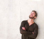 Laughing handsome man with arms crossed looking up Royalty Free Stock Photos