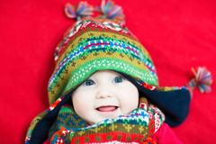 Laughing happy baby in a colorful knitted hat and scarf Stock Image