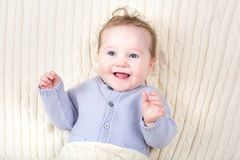Laughing happy baby in a knitted blanket Stock Images