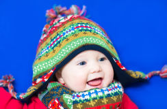 Laughing happy baby wearing a funny knitted hat an Stock Photography