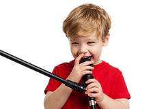 Cute Boy Singing. Laughing happy boy singing into a microphone, shot in the studio on a white background Stock Images