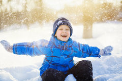 Laughing happy boy, sitting in the snow park. Royalty Free Stock Photography