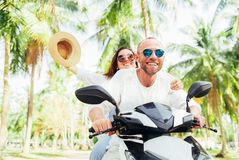 Laughing happy couple travelers riding motorbike during their tropical vacation under palm trees. Woman raised hand with hat up royalty free stock photo