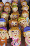 Laughing happy girl statues. Laughing gnomes made of pottery sold in a Thai market royalty free stock images