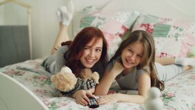Laughing happy mother and cute daughter watching funny cartoon movie on TV while lying on bed at home in the morning and. Laughing happy mother and cute daughter stock footage
