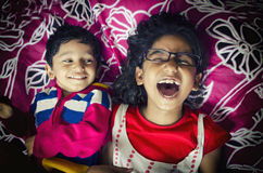 Laughing happy sibling children playing having fun on bed Royalty Free Stock Photography
