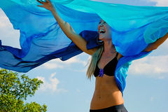Laughing happy woman. With arms up outdoors with blue cloth floating in air above her. Wearing a bikini top Stock Photos