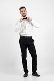 Laughing happy young bearded elegant man adjusting bow tie looking at camera Royalty Free Stock Photo