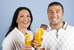 Laughing healthy couple with oranges juice Royalty Free Stock Images