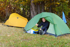 Laughing hiker woman is resting in tent in autumn mountains. Stock Image