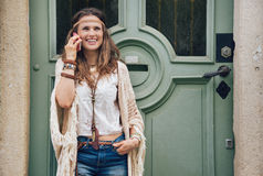 Laughing hippie woman in boho clothes talking cell phone Stock Photos