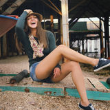Laughing hipster girl portrait under the old pier on a sea beach. Royalty Free Stock Images