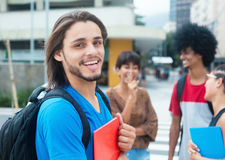 Laughing hipster male student with group of multi ethnic young a Stock Image