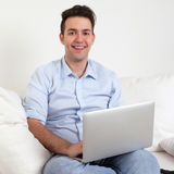 Laughing hispanic guy with notebook on a sofa Royalty Free Stock Photos