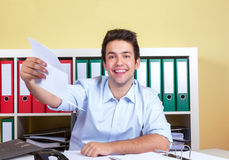 Laughing hispanic guy at office with letter Stock Photography