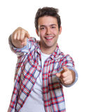 Laughing hispanic guy pointing with both hands at camera Royalty Free Stock Image