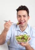 Laughing hispanic guy on a sofa eating salad Stock Image