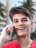 Laughing hispanic guy talking at phone. With buildings of the city in the background Stock Photos