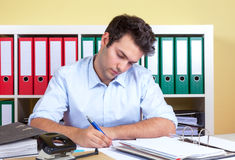 Laughing hispanic guy writing a message at office Royalty Free Stock Photos