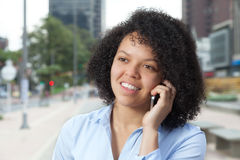 Laughing hispanic woman in the city talking at phone Royalty Free Stock Photography