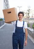 Laughing hispanic worker carries a box Stock Image