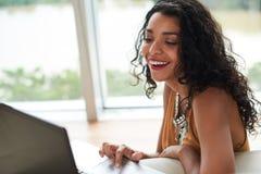 Binge watching. Laughing Hispanic young woman watching comedy series on her laptop royalty free stock photo