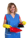Laughing housewife with blond hair sweeping with a broom Stock Photo