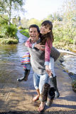 Laughing husband carrying wife through shallow stream.  Royalty Free Stock Photo