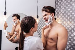 Husband laughing while his wife putting shaving foam on his face. Laughing husband. Husband laughing while his appealing young wife putting shaving foam on his stock photography
