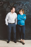 Laughing husband and pregnant wife posing against big blackboard Stock Image