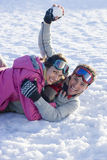 Laughing husband and wife having snowball fight stock image