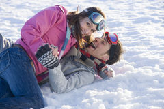 Laughing husband and wife laying in snow Stock Photo
