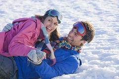 Laughing husband and wife laying in snow Royalty Free Stock Images