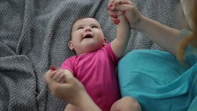 Laughing infant child getting massage by mother stock footage