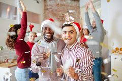 Santa friends. Laughing intercultural guys with champagne enjoying xmas party with friends Royalty Free Stock Photo