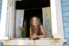 Laughing joyful little girl looking out from the window wide open Royalty Free Stock Images