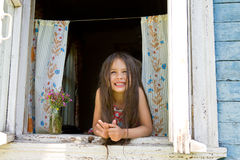 Laughing joyful little girl looks out from the window wide open Royalty Free Stock Photos