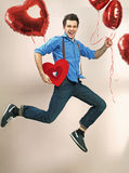 Laughing and jumping man with valentine's balloons. Laughing and jumping guy with valentine's balloons Royalty Free Stock Photography