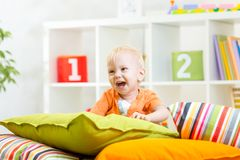 Laughing kid boy playing on pillows Royalty Free Stock Photography