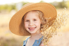 Laughing kid girl wearing hat outdoors. Portrait of laughing kid girl playing outdoors Royalty Free Stock Photography